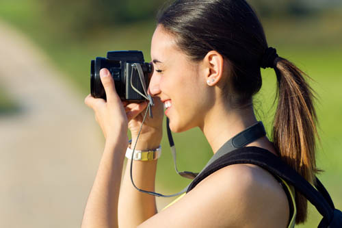 Portrait of Happy Young girl taking photos in the field